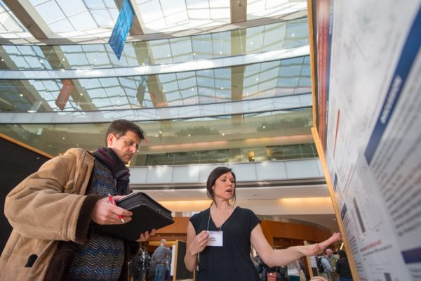 two people looking at a poster at a science conference